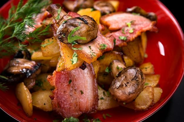 Жареный картофель с беконом и грибами на тарелке