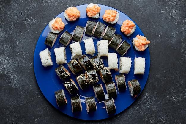 Набор для суши, на синей тарелке, на темном