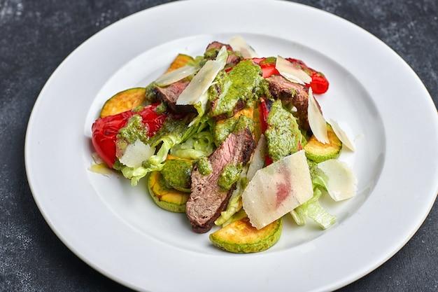 暗いテーブルに対して、子牛肉、焼き野菜、ピーマン、ズッキーニ、パルメザンチーズの白いプレート上の温かいサラダ