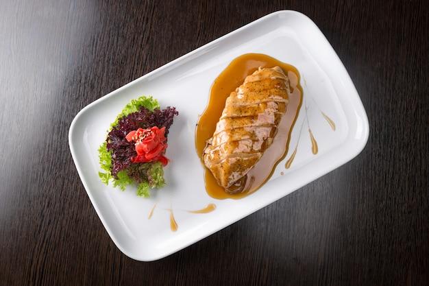 フライドチキンフィレ、スライス、野菜、ソース、ボード上の白いプレート。上面図
