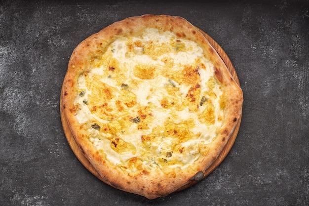 Четыре сырная пицца на светлой деревянной доске, на темном бетонном фоне