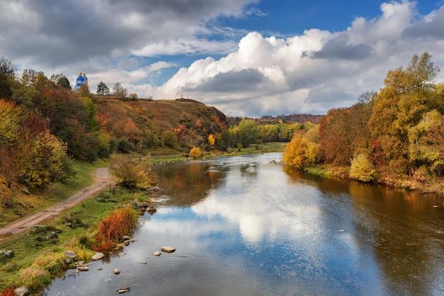 葉のある木で覆われた美しい川岸の秋の川