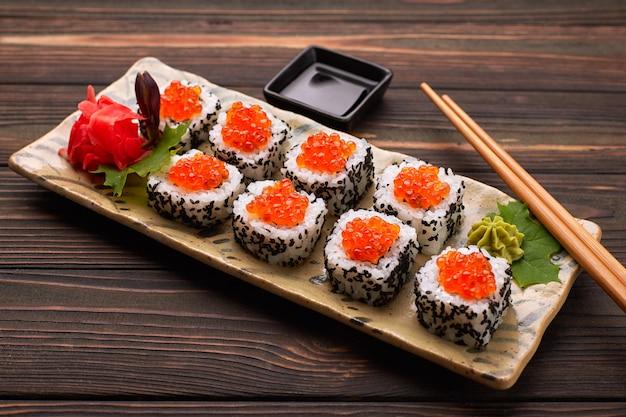 Суши-ролл с красной икрой на тарелке с васаби, имбирем, кленовыми листьями и палочками для суши, на деревянном фоне
