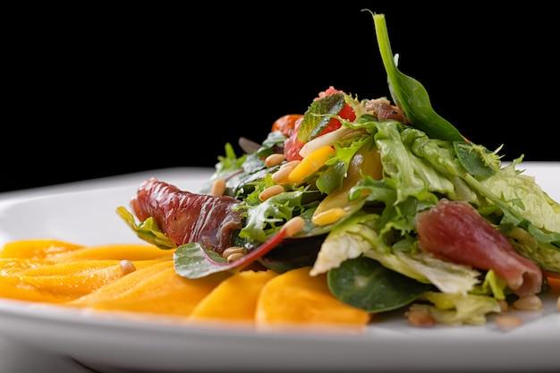 Салат из манго с вяленым мясом, грейпфрутом, кедровыми орешками и мятой на белой тарелке