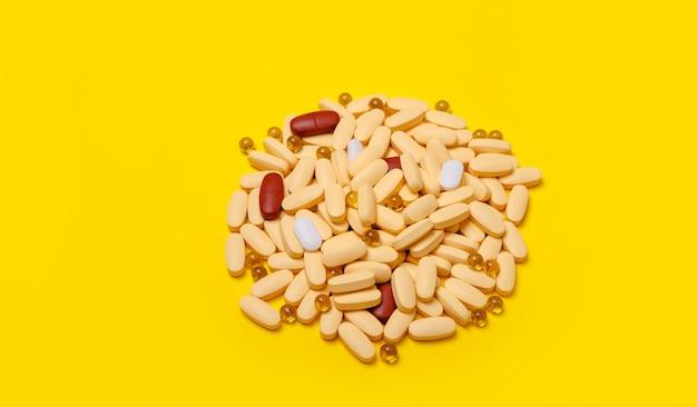 Горсть разноцветных таблеток на желтом фоне
