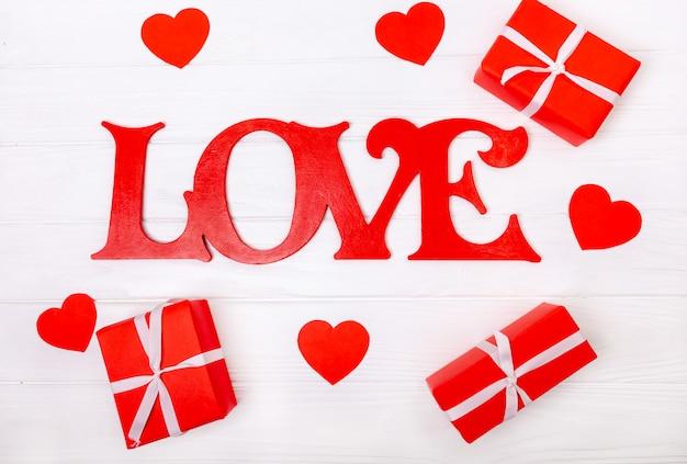 Любовь надпись с сердечками и подарками на деревянном белом фоне