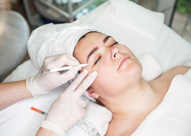 Врачи руки в перчатках касаются лица женщины. процедура против морщин