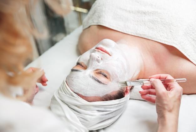女性はスパサロンで美容師によってフェイスマスクを取得します。顔の剥離マスクを適用する美容師。