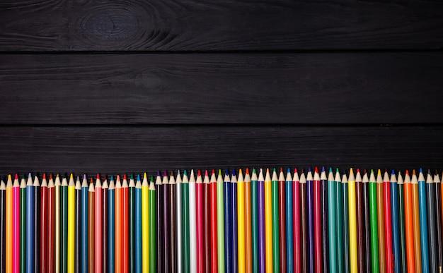 黒い木製のテーブルに色鉛筆のセット。印刷用品