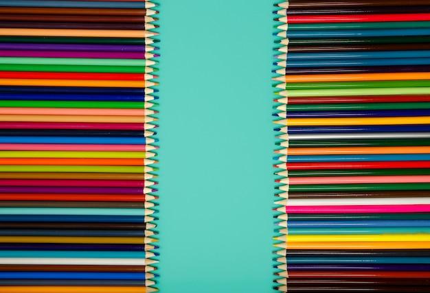 青いテーブルに虹のすべての色の色鉛筆