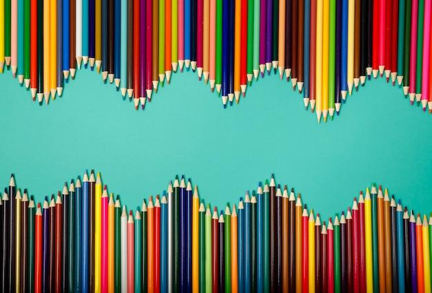 青い背景に分離された波に配置されたカラフルな鉛筆
