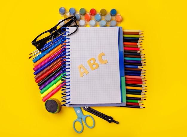 黄色のテーブルに学用品。学校のコンセプトに戻る