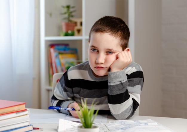 オンライン教育と遠隔学習の男子生徒が学校の宿題