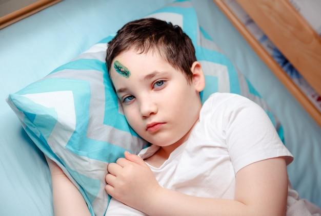 額に怪我をした子供がベッドに横になっています。その少年は頭の傷に腹を立てている。家の安全上の注意とテクニックの概念