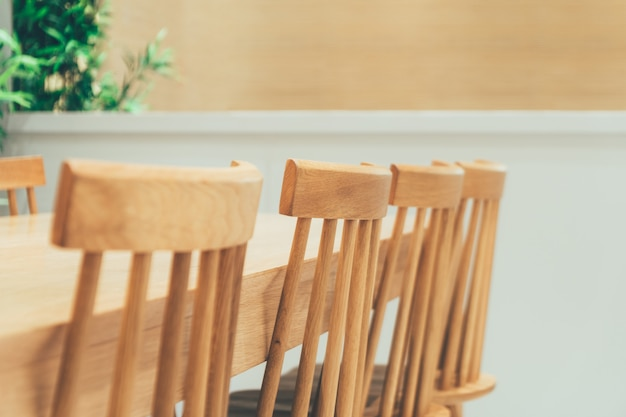Ряд классических и уютных натуральных деревянных виндзорских стульев и обеденного стола в красивой минималистичной комнате с растениями.