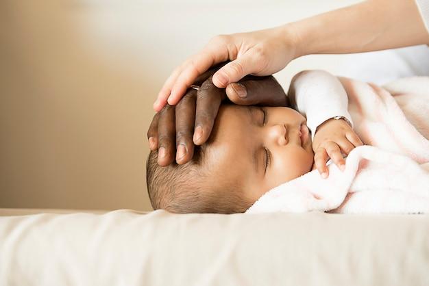 幸せな家族、母親と父親の睡眠赤ちゃん