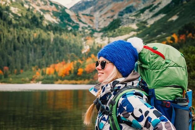 女性は自由を感じ、山で金の秋の自然を楽しむ
