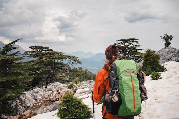 山の風景を見て女性バックパッカー