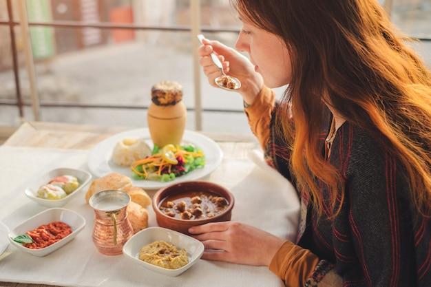Женщина ест турецкую еду из фрикадельки и шашлык