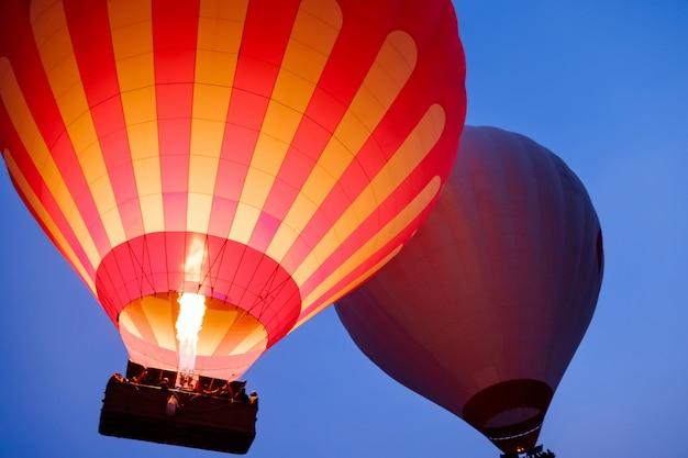 日の出のカッパドキアの風景の上を飛んで美しい熱気球