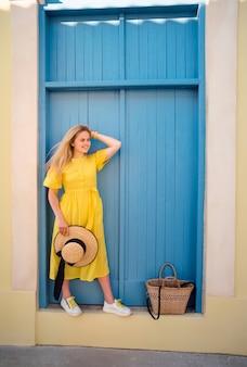 Женщина, идущая в желтом платье в старом городе пафоса