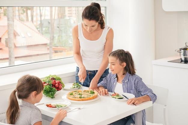 Мать готовит здоровую еду для детей