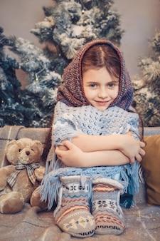 Милая маленькая девочка в теплом шарфе ждет рождество