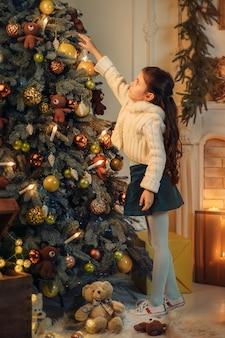 クリスマスツリーを飾る幸せな子供