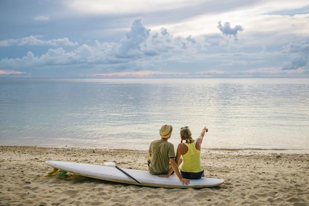 夕暮れ時のビーチでパドルボードと幸せなカップル
