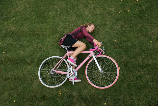 Взгляд сверху женщины с велосипедом на траве
