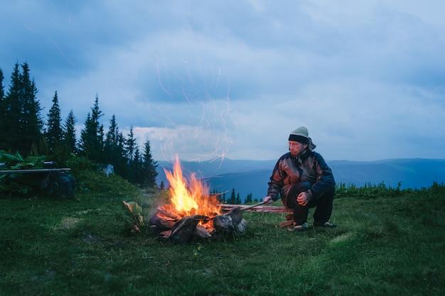 山の夕暮れ時にキャンプの火の近くに座っている観光客