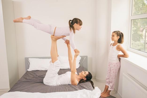 Мать с детьми делает упражнения йоги в постели