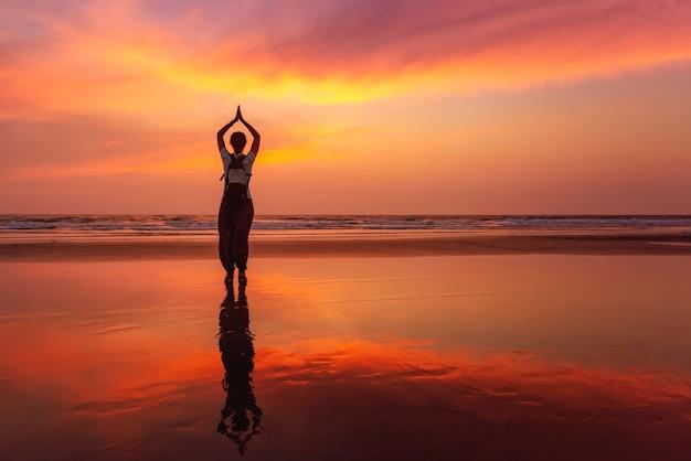 日没の水ゴアビーチに美しいヨガ瞑想反射