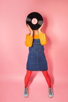 ピンクの背景にビンテージビニールでレトロなスタイルのファッショナブルな女性