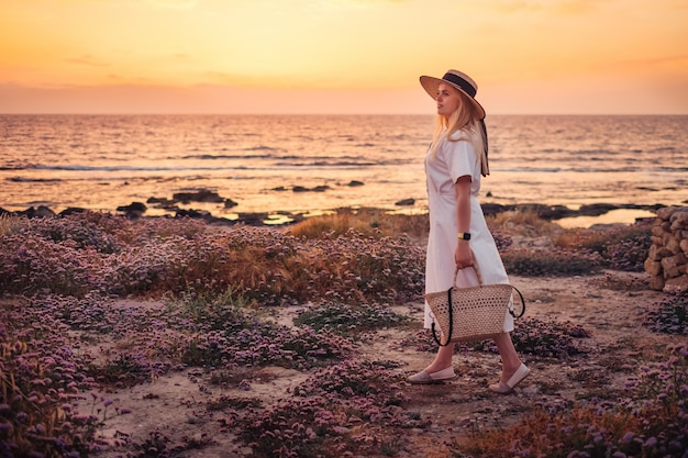 キプロスへの旅行と海の夕日を楽しむ女性