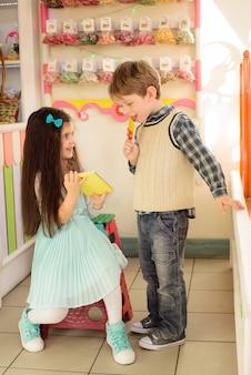 Маленькая девочка показывает мальчику, как использовать планшет