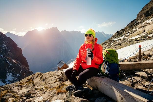 女性は登山後の山の風景と飲料水を楽しむ