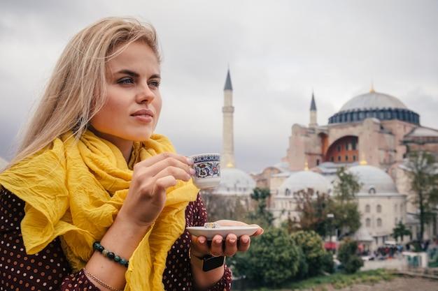 Женщина пьет турецкий кофе возле собора святой софии, стамбул