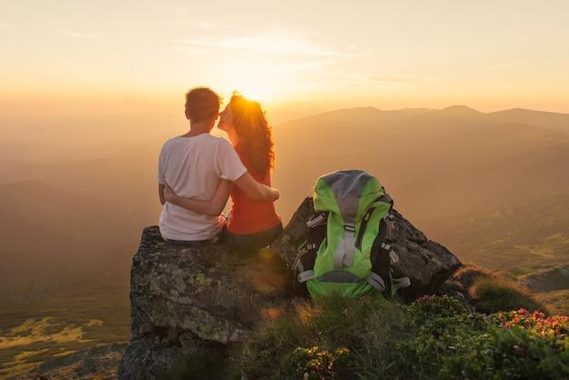 若いカップルが山で一緒に美しい夕日を楽しむ