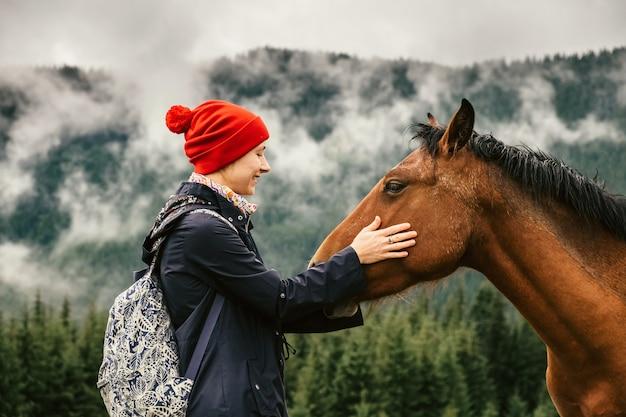 Женщина касается лица лошадей на открытом воздухе