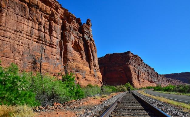 鉄道はユタ州の赤い山に沿って走っており、遠くにはレールの間の人がいます。米国ユタ州
