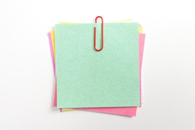 赤いペーパークリップと白で隔離されるカラフルなメモ紙ピン。