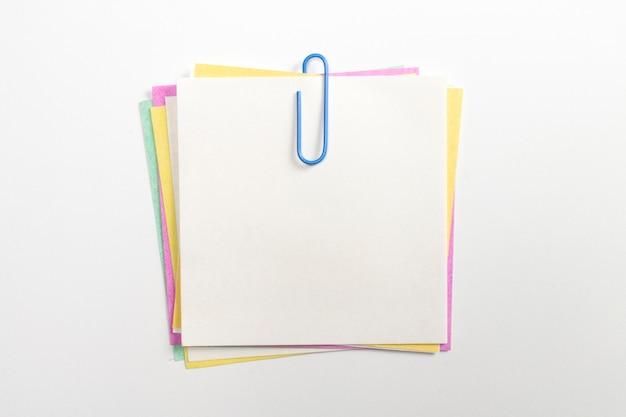 青いペーパークリップと白で隔離されるカラフルなメモ紙ピン。