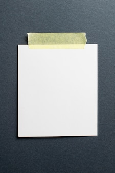 ソフトシャドウと黒のクラフトペーパーの背景に黄色のスコッチテープの空白のフォトフレーム