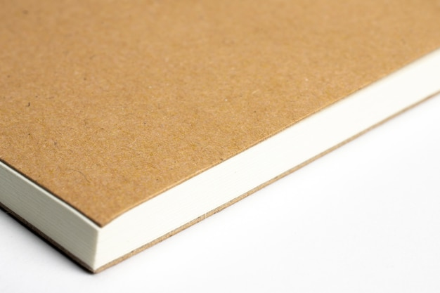 Макрос пустой углу ноутбука с картонной обложке на белом