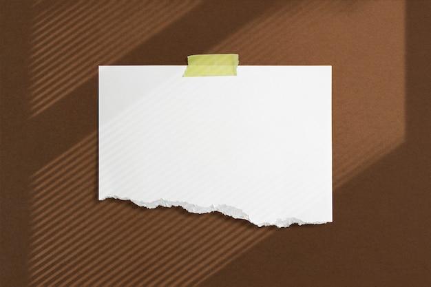 柔らかい窓の影のアドビで茶色の織り目加工の壁に粘着テープで接着された空白の破れた紙フレーム