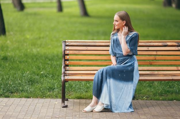 ベンチに座っている美しい少女、明るいドレスを着たブルネット、公園で晴れた日、公園で夏休み。日当たりの良い春