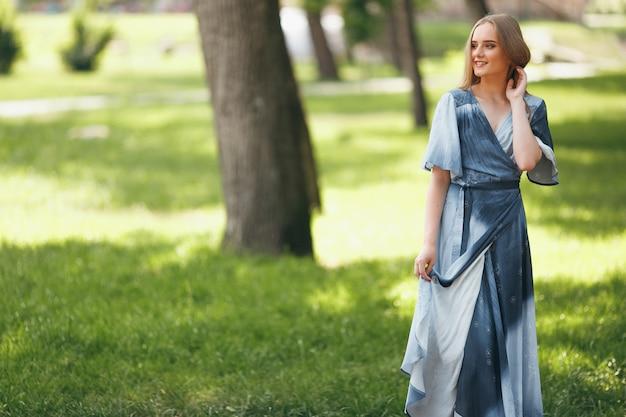 日当たりの良い春の公園でドレスでポーズをとるスタイリッシュな女の子。夏の美しい少女の陽気で幸せな肖像画