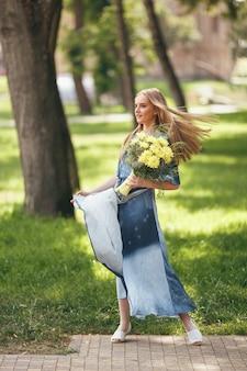 日当たりの良い春の公園でドレスでポーズをとるスタイリッシュな女の子。春に花束を持って立っている美しい少女の穏やかな肖像画
