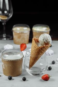 明るい背景にワッフルコーンのアイスクリーム。アイスクリームが溶けています。ワッフルコーンとイチゴ